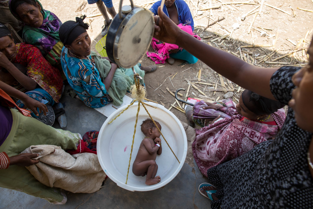 On 11 February 2016 in Ethiopia, a tiny baby boy sleeps while being weighed in a sling-scale during a nutrition screening at the UNICEF-supported community health post in Arago Nemano Kabele, Shalla Woreda, West Arsi Zone. Nearly 1 million children are in need of treatment for severe acute malnutrition in Eastern and Southern Africa, where two years of erratic rainfall and drought combined with one of the most powerful El Niño events in 50 years have put millions of children at risk of hunger, water shortages and disease. The situation is exacerbated by rising food prices, which have forced families to forgo meals, sell off their assets and take other drastic measures in order to survive. Across Ethiopia, millions of children are struggling to cope with food insecurity, lack of water, disease and threats to their education and safety. Nearly 6 million children in the country are in need of food assistance. UNICEF, working with the Government, is helping to provide therapeutic food and therapeutic milk and other support in response to the drought emergency.