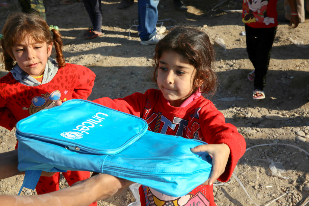 On 25 November, Ruqaya, 7, displaced from Ramadi, collects a new UNICEF school bag in an IDP camp in Al Ghazalia, Baghdad. In the last year, UNICEF has facilitated the distribution of learning materials to more than 346,000 children across the country. The impact of conflict, violence and displacement has devastated Iraq's education system. Nearly 2 million children are currently out of school, with an additional 1.2 million at risk of dropping out. Almost 1 in 5 schools across the country cannot be used as a result of the ongoing conflict. Of the schools that remain in use, thousands are overburdened, with large class sizes and many schools operating in multiple shifts.