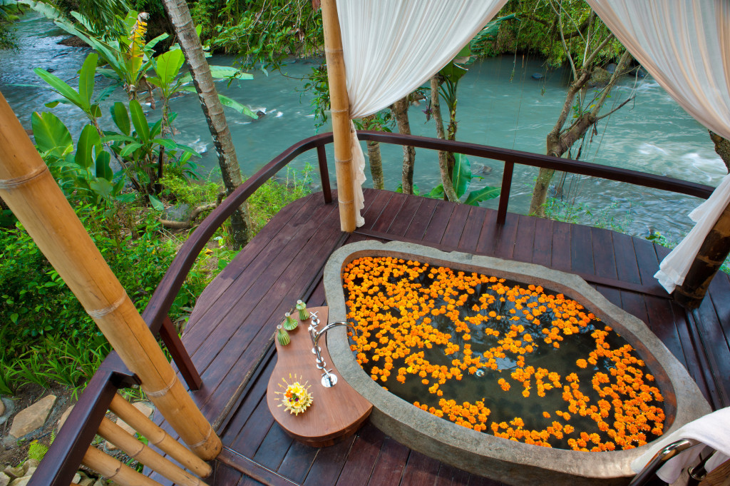 The healing center at Fivelements features a private, hewn-boulder bath overlooking the Ayung River.
